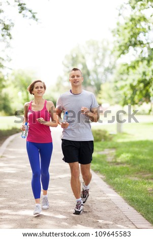 Couple jogging in the park - stock photo