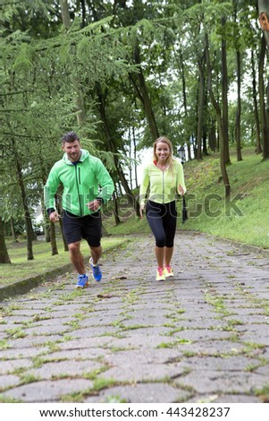 couple jogging outside.Athletic attractive people jogging in summer rainy day - stock photo