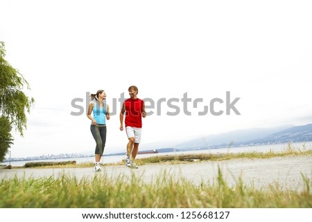 couple jogging outside, grass visible on the foreground, mountains and bright sky visible in the background - stock photo