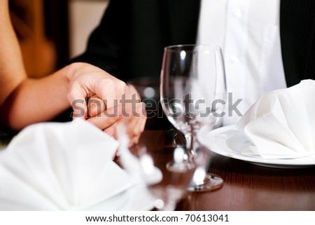Couple, just hands to be seen, is holding hand while waiting for their food and drinks in a restaurant. - stock photo