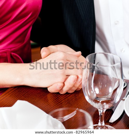 Couple, just hands to be seen, is holding hand while waiting for their food and drinks in a restaurant - stock photo