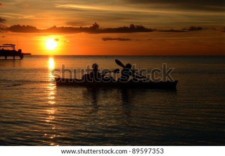 Couple kayaking at beautiful sunset at tropical location of Florida keys. - stock photo