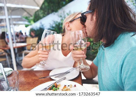 Couple kiss and celebrate engagement at lunch - stock photo