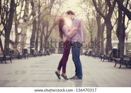 Couple kissing at alley in city. - stock photo