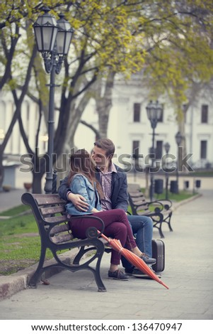 Couple kissing at the bench at alley. - stock photo