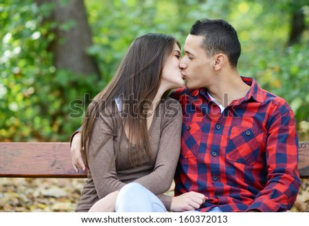 Couple kissing at the bench in park - stock photo