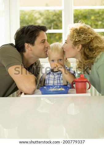 Couple kissing baby boy - stock photo