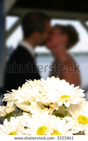 Couple kissing behind a group of wedding bouquet - stock photo
