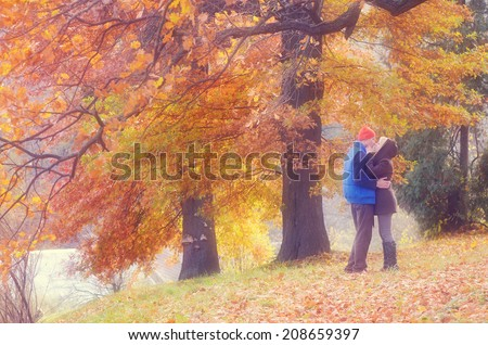 Couple kissing in autumn park on a sunny day. Soft effect. Color toning - stock photo