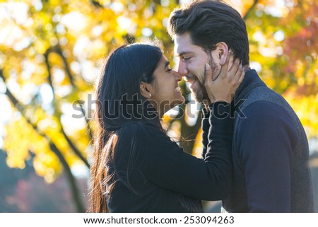 Couple kissing in front of a autumn tree - stock photo