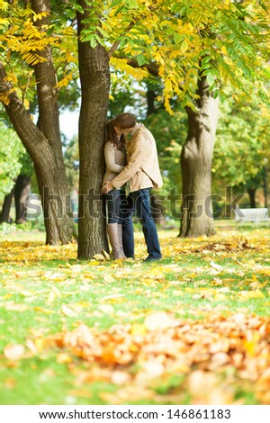 Couple kissing in park on a fall day - stock photo