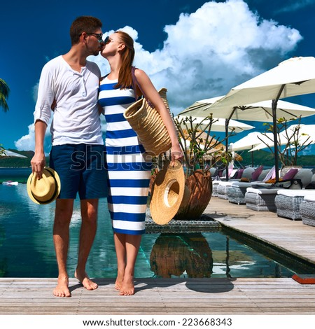 Couple kissing near poolside jetty at Seychelles - stock photo