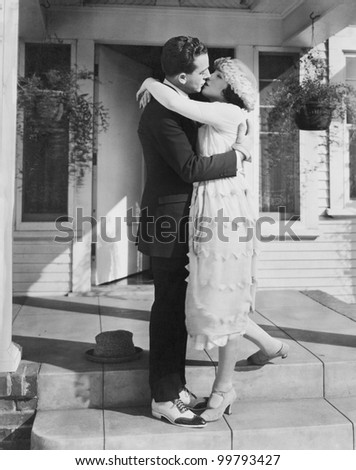 Couple kissing on front porch - stock photo