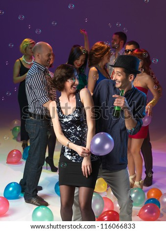 couple laughing and dancing, in front of ogroup of men and women at party, with balloons and bubbles - stock photo