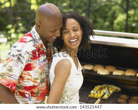 Couple laughing and having barbecue together - stock photo