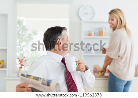 Couple laughing toghethe in kitchen before work with man holding mug and newpaper - stock photo