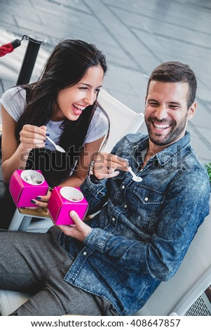 Couple laughing while eating ice cream in the city - stock photo