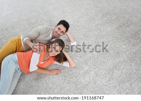 Couple laying on carpet of brand new renovated flat - stock photo
