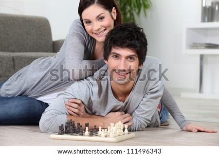 Couple laying on the floor playing chess - stock photo