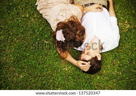 couple laying on the grass - stock photo