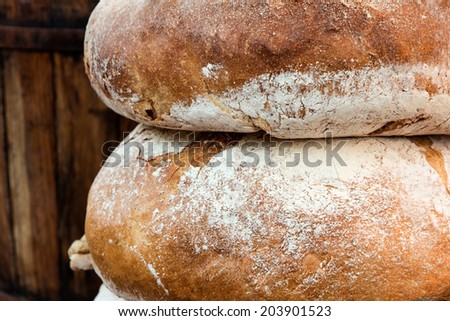 Couple loafs of rye bread lying near barrel - stock photo