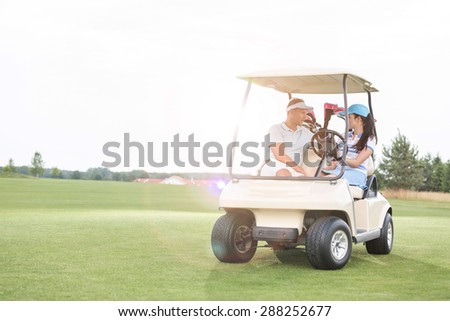 Couple looking at each other while sitting in golf cart against clear sky - stock photo