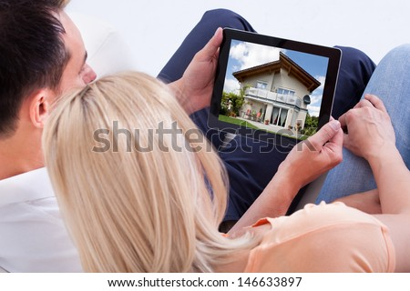 Couple Looking At House On Digital Tablet's Screen - stock photo