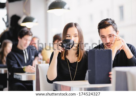 Couple looking at photos on tablet computer in cafe - stock photo