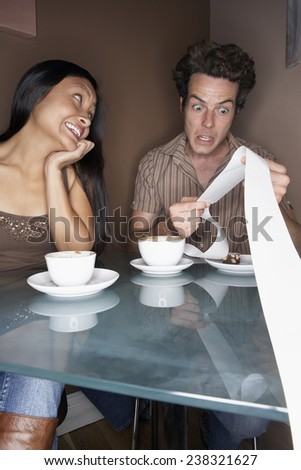 Couple Looking at Receipt - stock photo