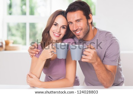 Couple looking at the camera with a coffee and smiling - stock photo
