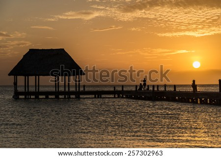 Couple looking at the sun going down on a wooden pier with a hut. - stock photo