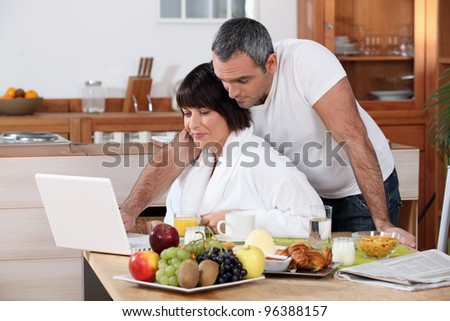 Couple looking at their laptop during breakfast - stock photo