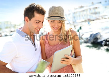 Couple looking at tourist information on tablet - stock photo