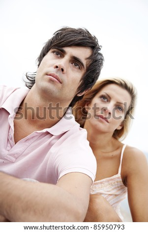 couple looking seriously into the distance - stock photo