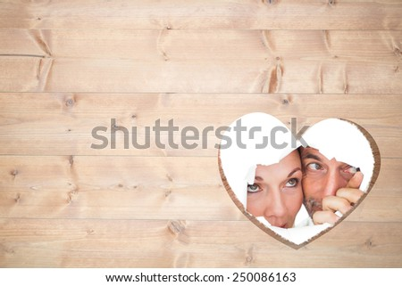 Couple looking through torn paper against heart in wood - stock photo