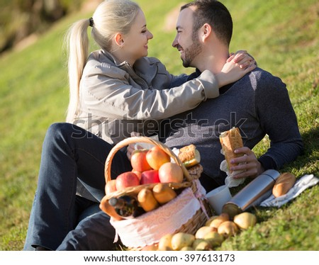 Couple lounging in sunny spring day at picnic outdoors - stock photo