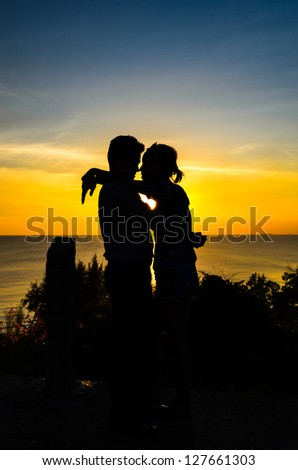 Couple love on the top of view with sunrise silhouette style - stock photo