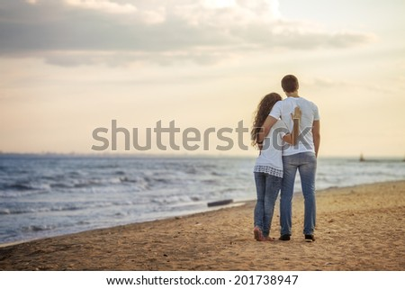 Couple Lovers walking on the beach - stock photo