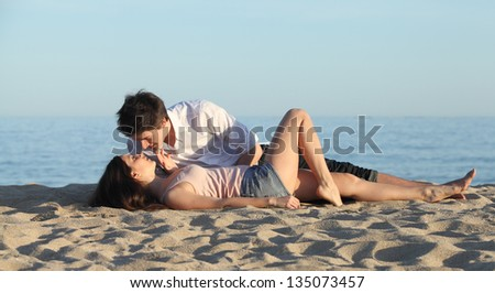 Couple lying and flirting on the sand of the beach with the sea in the background - stock photo