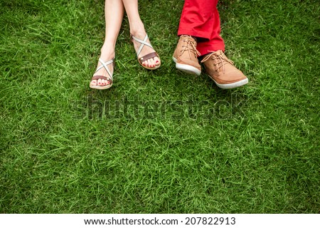 Couple lying and relaxing on the grass. Legs, top view, text space. - stock photo
