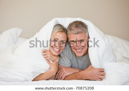 Couple lying down in their bed at home - stock photo