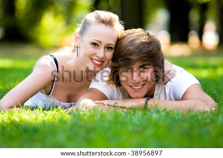 Couple lying down on grass - stock photo