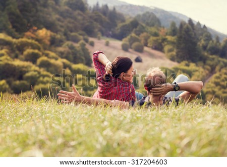 Couple lying in green grass on the forest hill - stock photo
