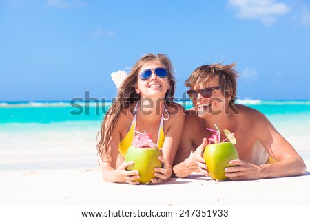 couple lying on a tropical beach in Barbados and drinking a coconut cocktail - stock photo
