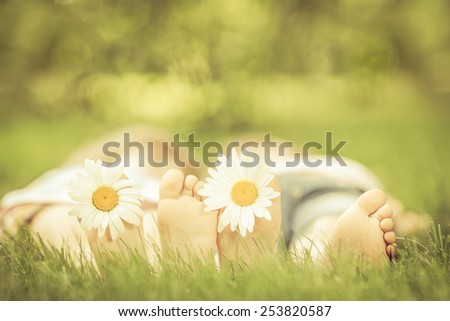 Couple lying on green grass. People having fun outdoors in spring park. Retro toned image - stock photo
