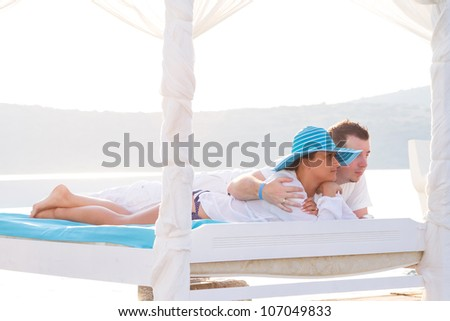 Couple lying on luxury white bed at the sea - stock photo