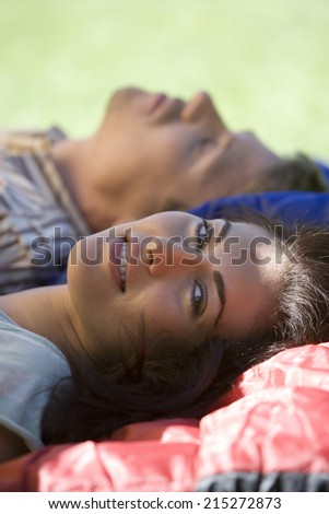 Couple lying on sleeping bags in tent entrance on garden lawn, focus on woman in foreground, smiling, side view, portrait - stock photo
