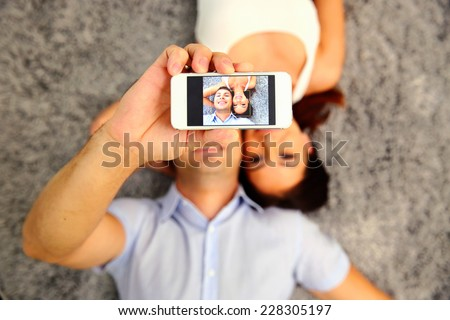 Couple lying on the floor and making selfie photo on smartphone. Focus on smartphone - stock photo