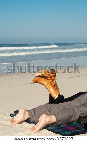 Couple lying on the sandy beach on holiday in winter. Woman is wearing black pants with brown leather boots and the man is wearing grey linen pants. He's got dirty feet from sand. - stock photo