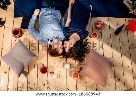 couple lying on wood floor with pillows and sweets - stock photo